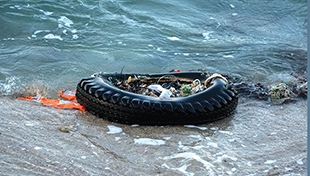Tire with trash in the ocean